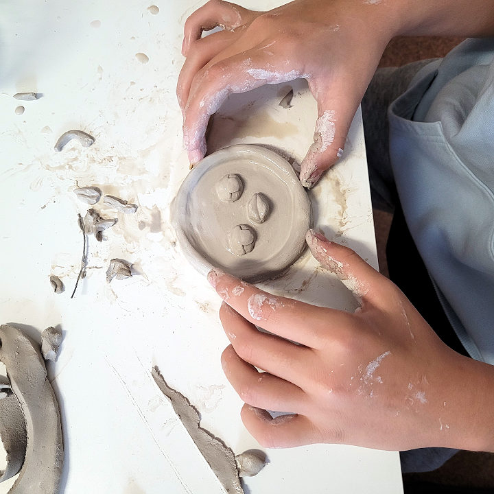 Dziecko lepi z gliny figurkę